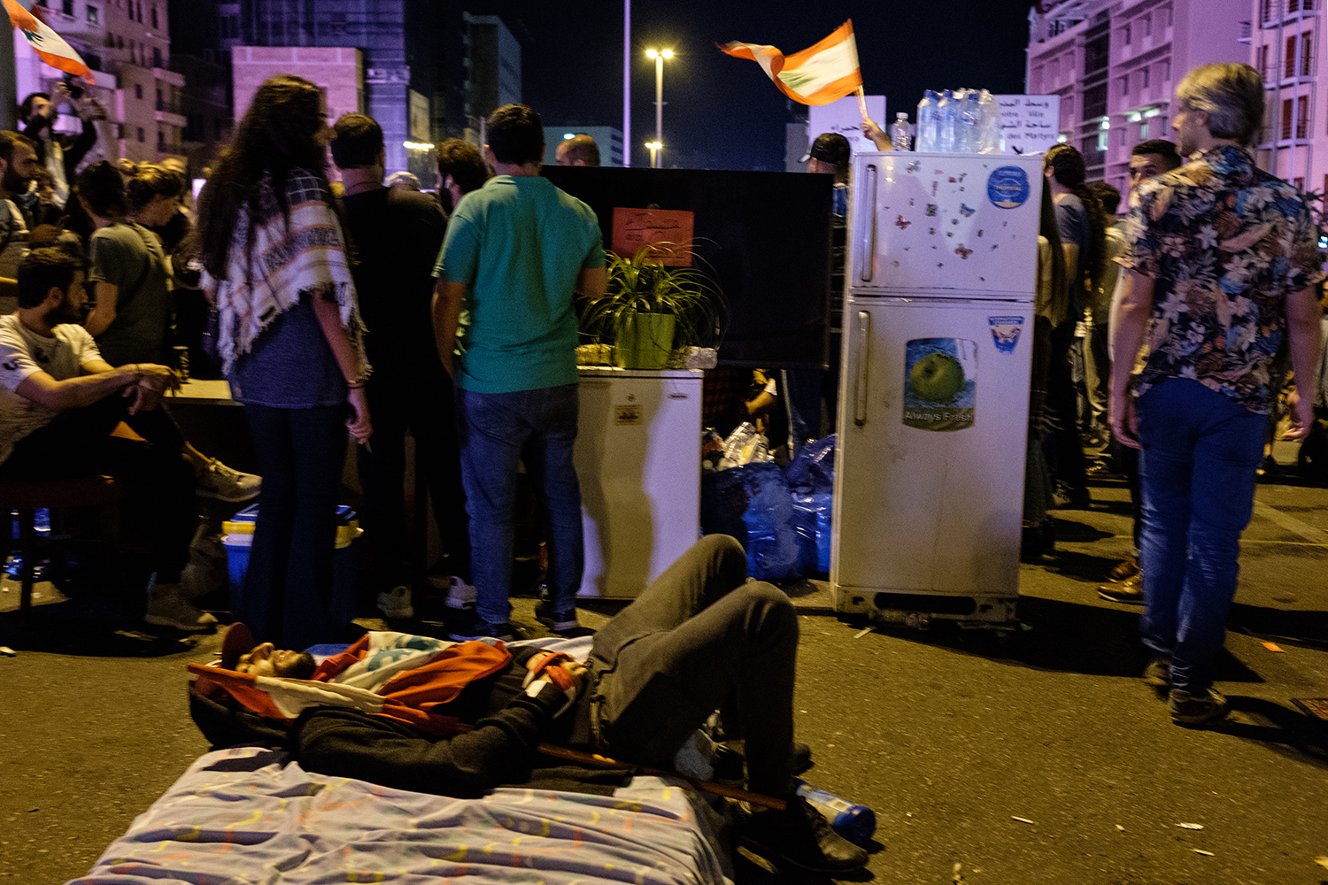 A protester gets comfortable on a mattress brought to the roadblock on the Gemmayze side of the Ring Bridge on Oct. 27. The site was listed on Airbnb for alt=