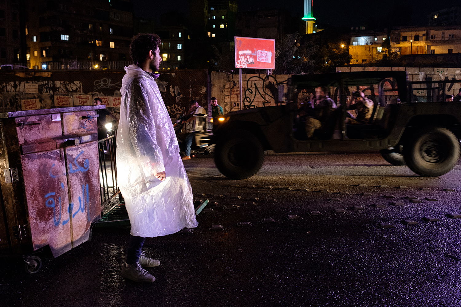 "A protester stands at a roadblock to the Ring Bridge as an army truck passes on Oct. 28. Graffiti in Arabic on the garbage container behind the protester says ""the state's office."""