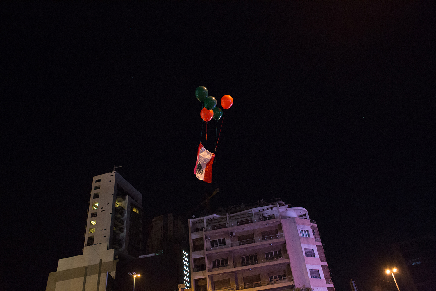 "Freed balloons carry the Lebanese flag into the sky at the Ring Bridge on Oct. 29, the night that Saad Hariri resigned as prime minister. ""Lebanon Rising"" in Arabic has become a popular hashtag on social media as the protests continue."