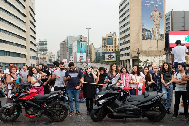 Protesters link arms to hold the line at a roadblock on the Ring Bridge in Beirut on Oct. 26.