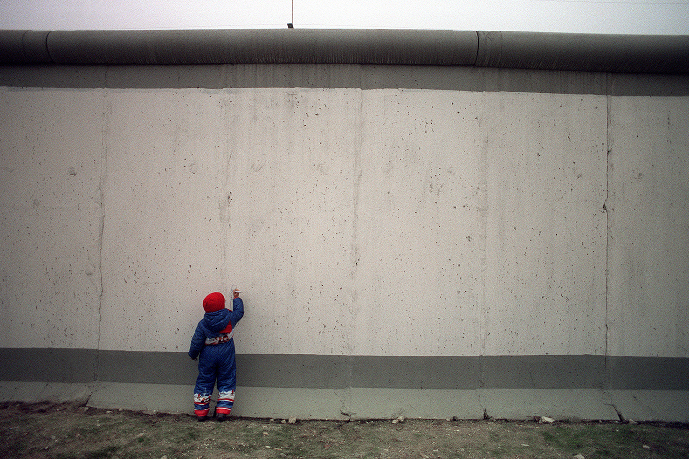 A boy draws on the blank east side of the Berlin Wall on Nov. 21, 1989, a few yards from the newly opened crossing at Potsdamer Platz. Patrick Hertzog/AFP via Getty Images