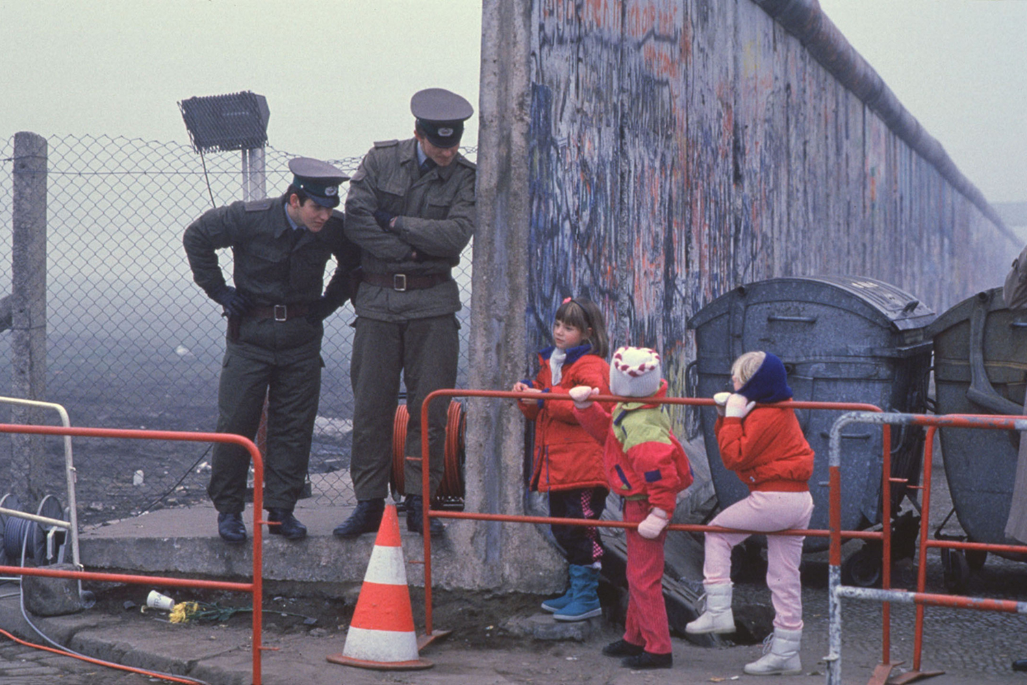West German schoolchildren on the way to school peer at East German border guards at a new opening in the Berlin Wall