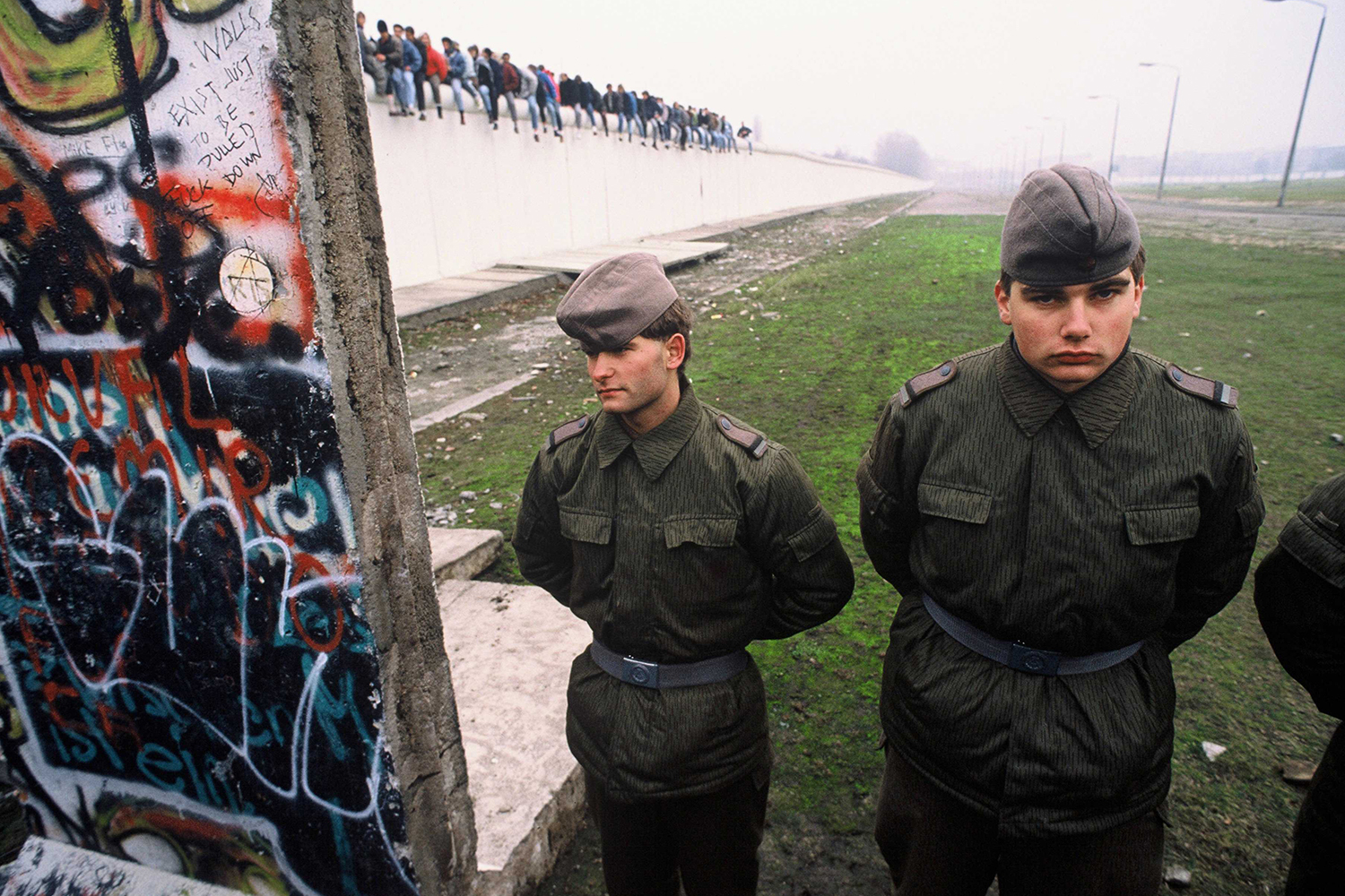 "East German border guards stand in a newly opened section of the Berlin Wall on Nov. 10, 1989. Atop the wall are celebrating East and West Germans who would have been shot only a few days before. The east-facing wall remains white, while the west-facing side is covered in graffiti. One message reads: ""Walls exist just to be pulled down."" Robert Wallis/Corbis via Getty Images"