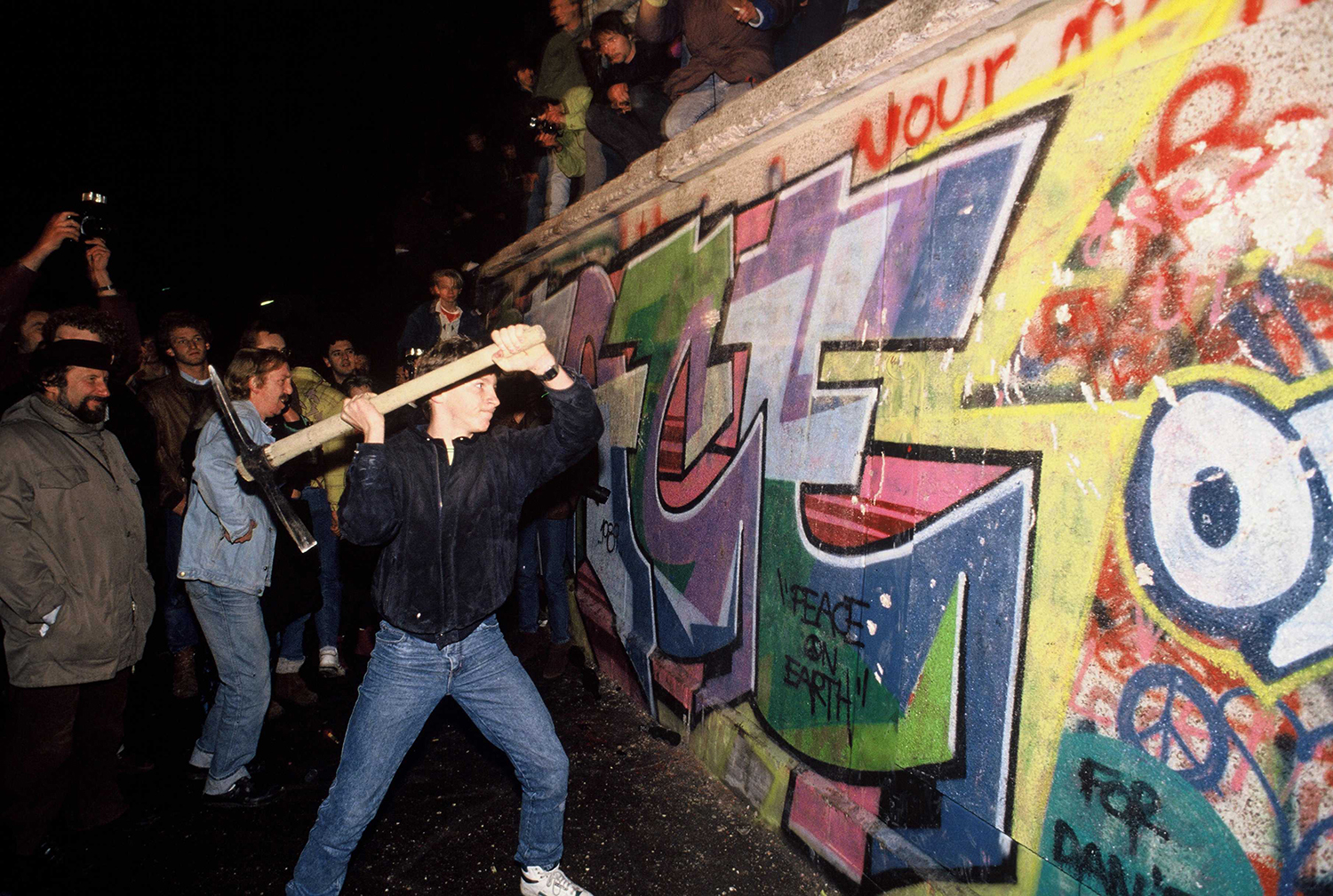 A man attacks the Berlin Wall with a pickax on the night of Nov. 9, 1989, as news spread that the East German government would start granting exit visas to anyone who wanted to go to the West. Robert Wallis/Corbis via Getty Images