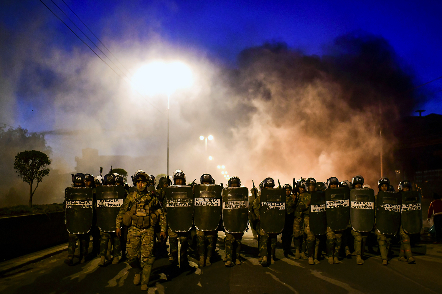 Bolivian militarized police take position as supporters Morales block a road outside Cochabamba on Nov. 18. RONALDO SCHEMIDT/AFP via Getty Images