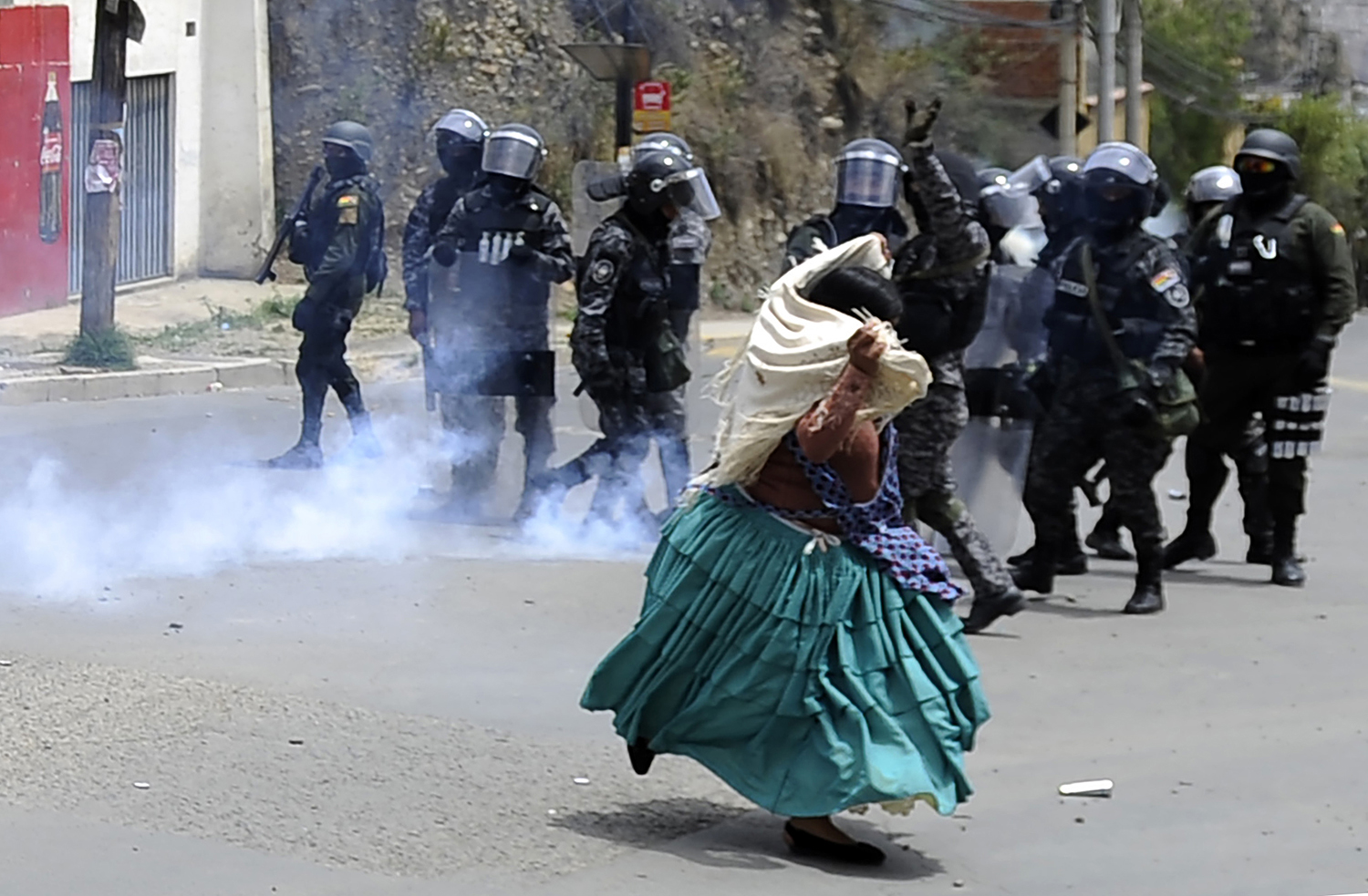 Riot police fire tear gas as an indigenous woman protests against a civic strike triggered by the result of the Oct. 20 election run in La Paz, Bolivia, on Oct. 29. JORGE BERNAL/AFP via Getty Images