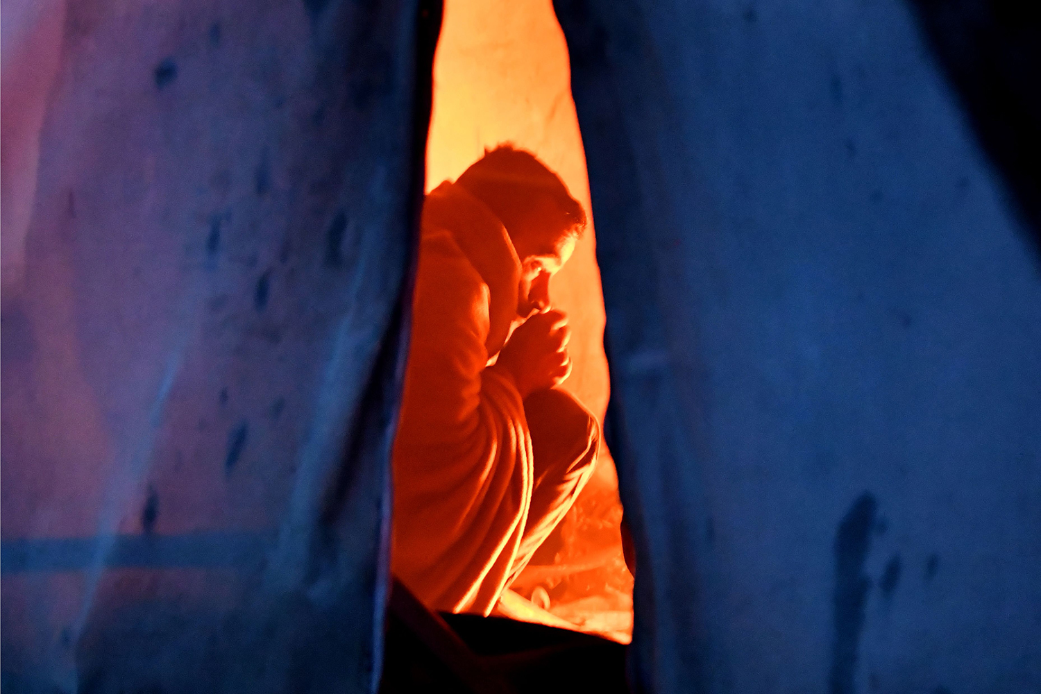 A migrant sits near a small fire inside a tent at camp Vucjak on the outskirts of the city of Bihac, in northern Bosnia, on Nov. 19. ELVIS BARUKCIC/AFP via Getty Images