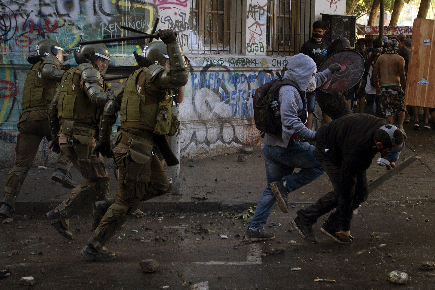 Riot police chase demonstrators during a protest against the government in Santiago on Nov. 19. CLAUDIO REYES/AFP via Getty Images