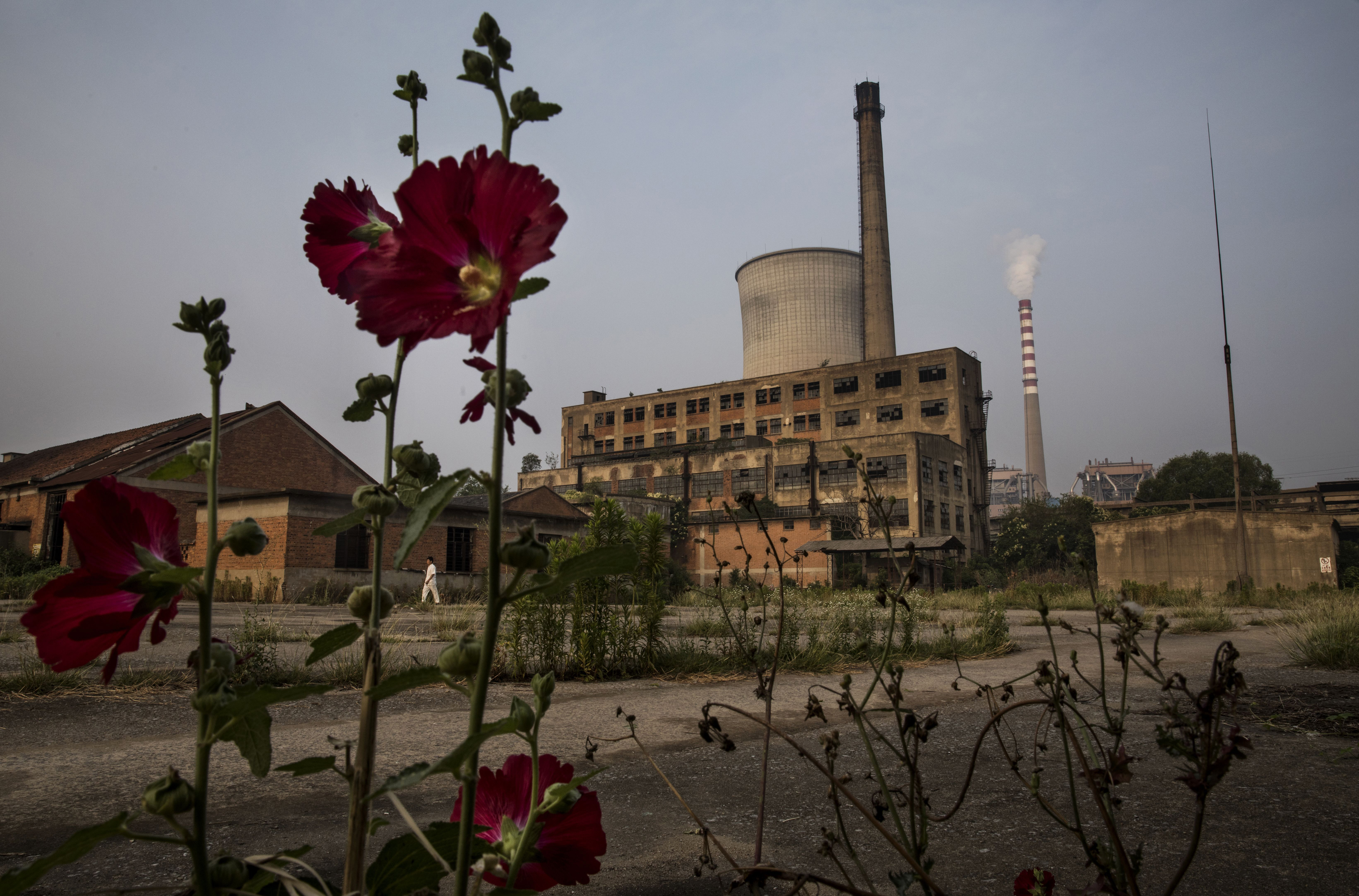 A smokestack from a coal fired power plant is seen near the site of a large floating solar farm project under construction on June 16, 2017 in Huainan, Anhui province, China.