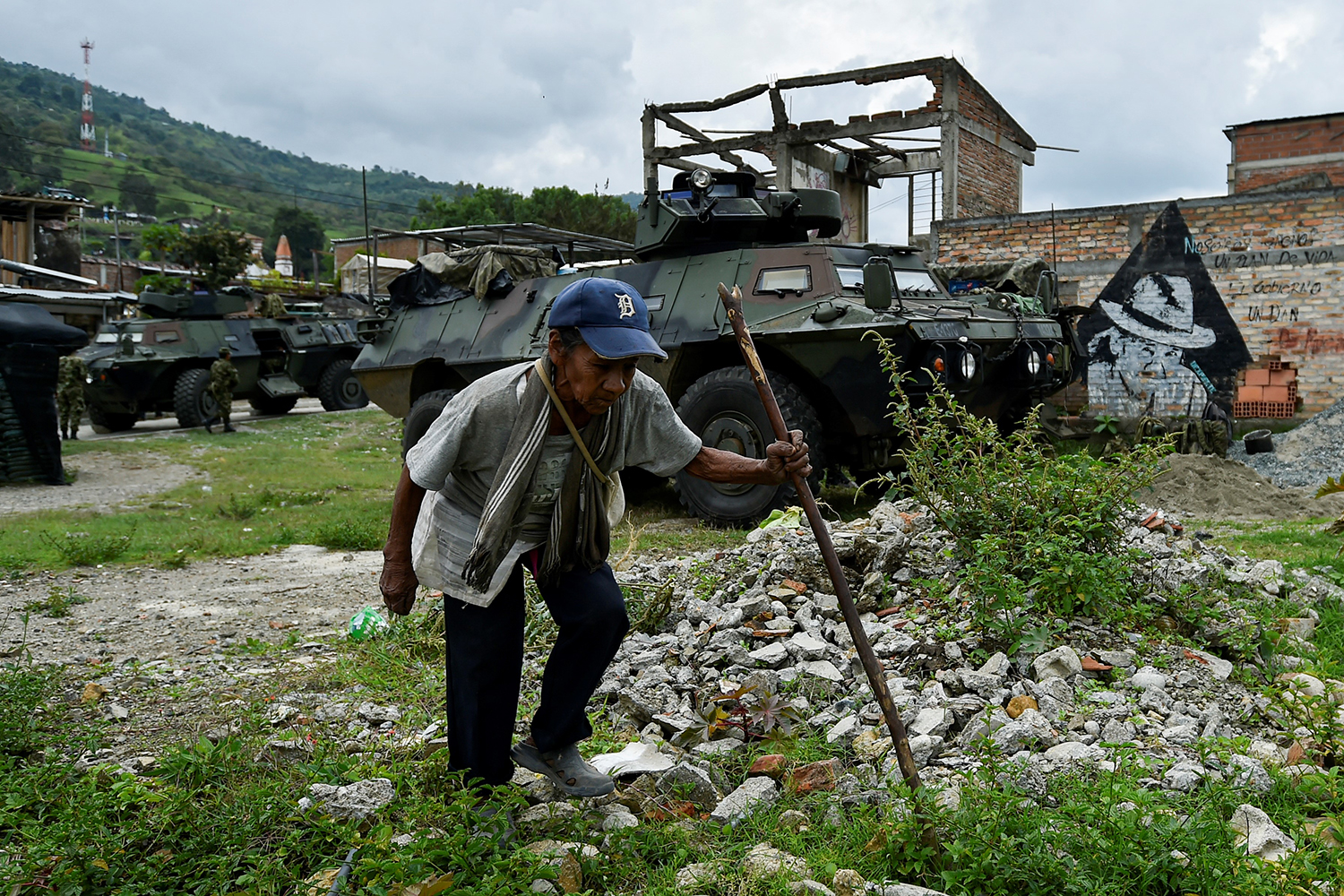 An indigenous woman walks next to a Colombian Army armored vehicle in Toribio, Colombia, on Oct. 30. Five indigenous guards were killed and six more injured during an attack authorities blamed on a dissident insurgent group that refused to join the country's peace accord. LUIS ROBAYO/AFP via Getty Images