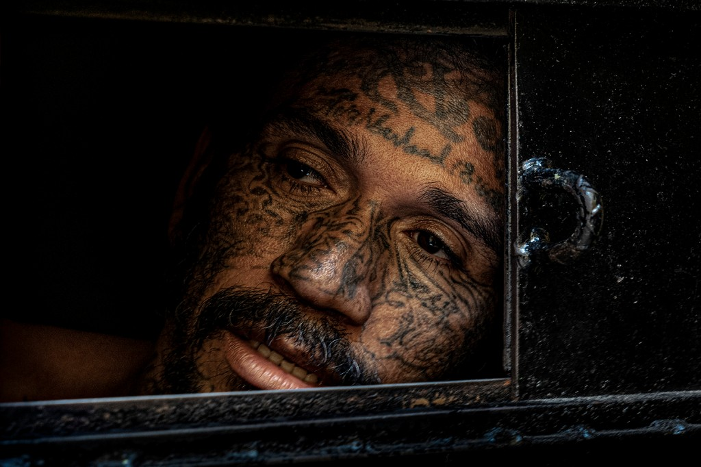 An inmate in solitary confinement looks out of his cell at the Penal San Francisco Gótera, one of the only mixed-gang prisons in El Salvador, on Nov. 8, 2018. The facility houses members of MS-13, La 18, Mao Mao, and Mirada Loca.