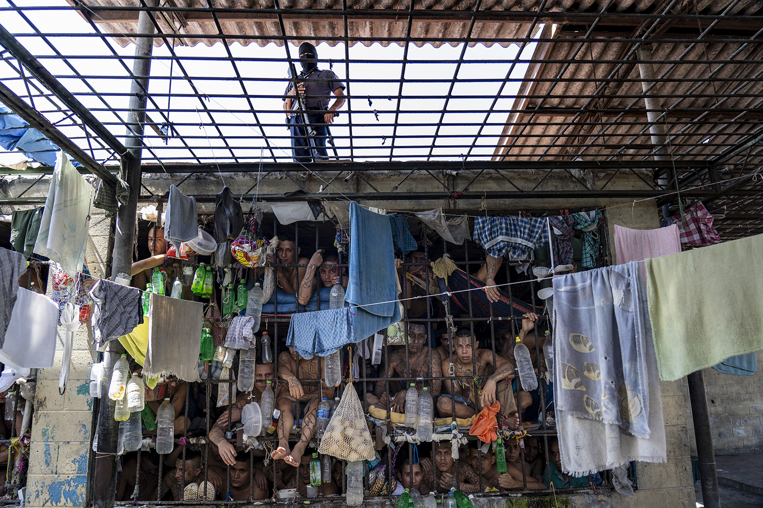 Inmates look out of an overcrowded cell while a prison officer wearing a balaclava to protect his identity stands guard above at the Penal Center of Quezaltepeque on Nov. 5, 2018.