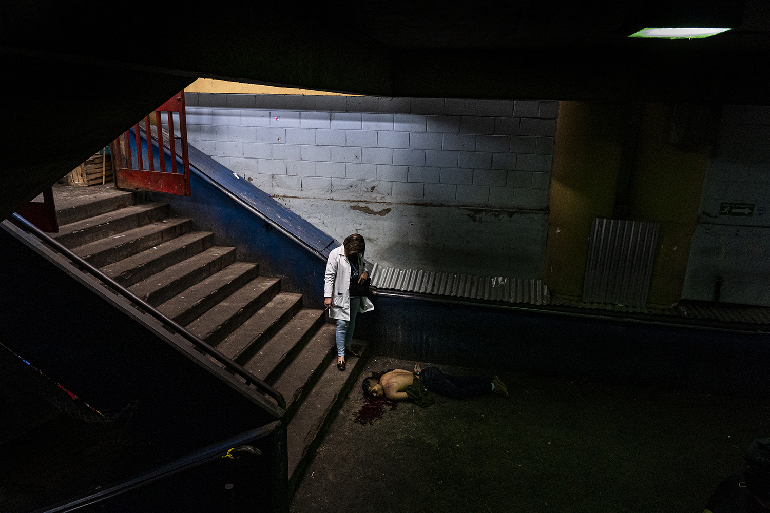 A forensic policewoman stands over a body in one of the busiest places in the capital—the San Salvador Central Market—on Sept. 25. The victim was handcuffed behind his back and shot seven times at around 10:30 in the morning, the National Civil Police reported.
