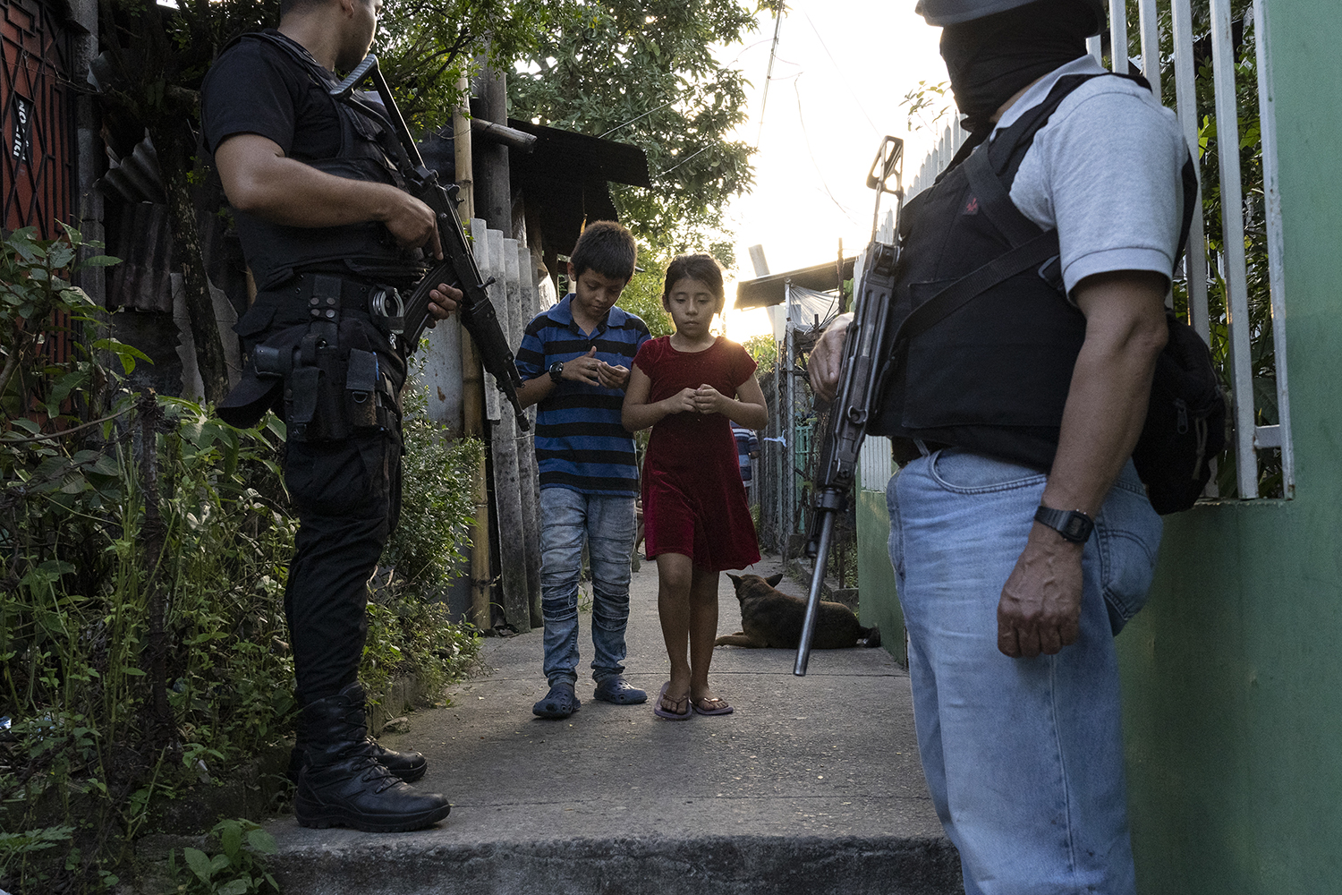 Children who live in a low-income neighborhood controlled by MS-13 pass by a police patrol in San Martín, San Salvador, on Nov. 5, 2018.