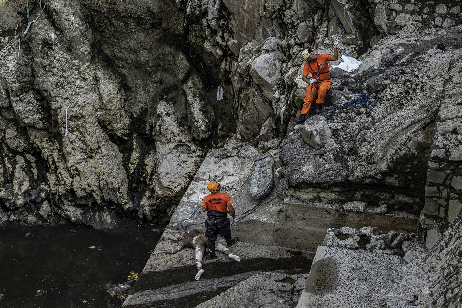The decomposed body of Byron Stanley Henríquez Funes is pulled out of a river at the dam by Las Mulas Bridge in the municipality of Ciudad Delgado, San Salvador, by emergency personnel on Sept. 24. He had been missing for three days.