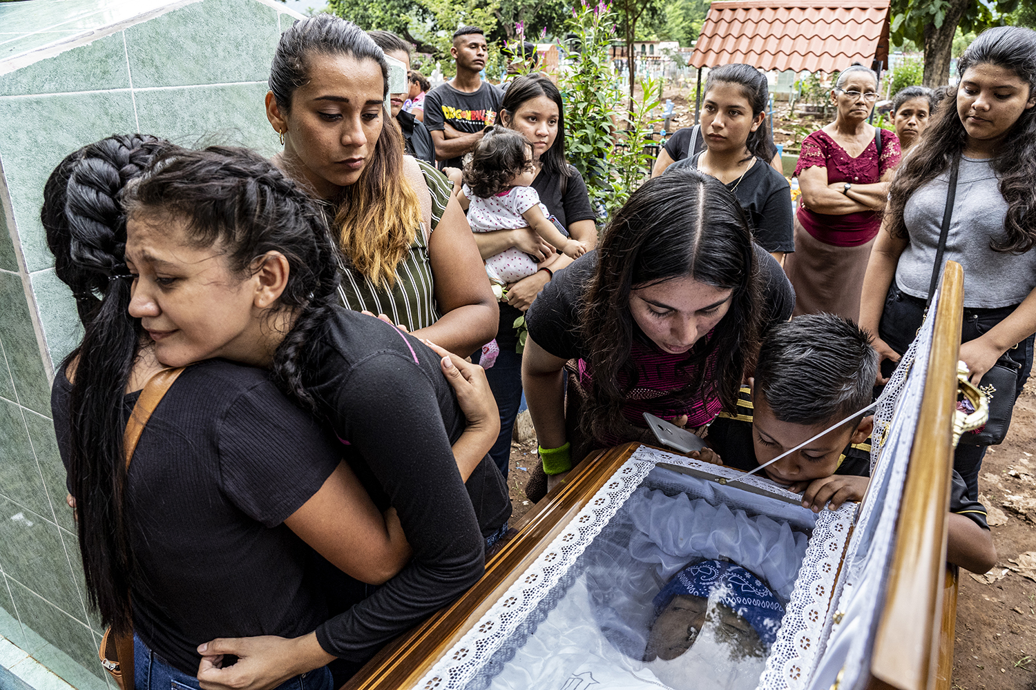 "Rivera's 19-year-old wife, whose name has been omitted to help protect her identity, left, reacts during his funeral on Sept. 27. Fellow gang members placed marijuana, a military medal, and a shirt reading ""Cara de Malo"" in his grave."