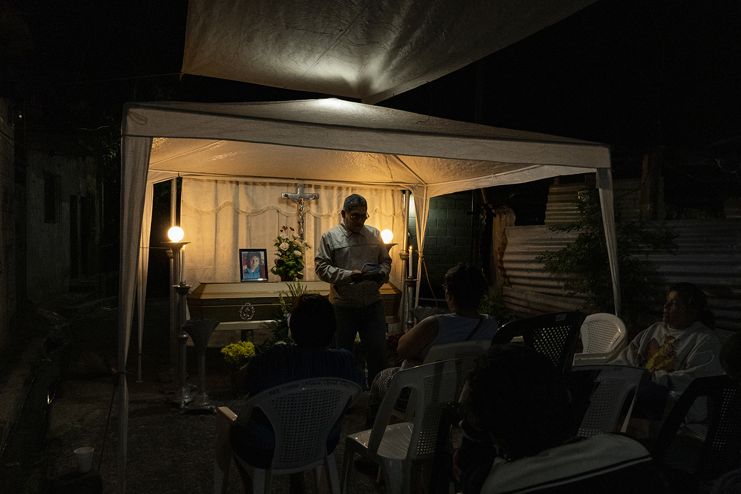 A priest reads from the Bible at the wake for 11-year-old José Luis Peréz Madrid in the Veracruz neighborhood of San Salvador on Nov. 30, 2018. The boy, who the attorney general's office says was killed in an area dominated by La 18 gang members, played with friends in a park near the demarcation line between the La 18 and MS-13 gangs before they were kidnapped by La 18. His two friends escaped, but José Luis was beaten, tortured, stabbed, and beheaded. At his wake, his family said he loved skateboarding, soccer, and the new President Nayib Bukele.