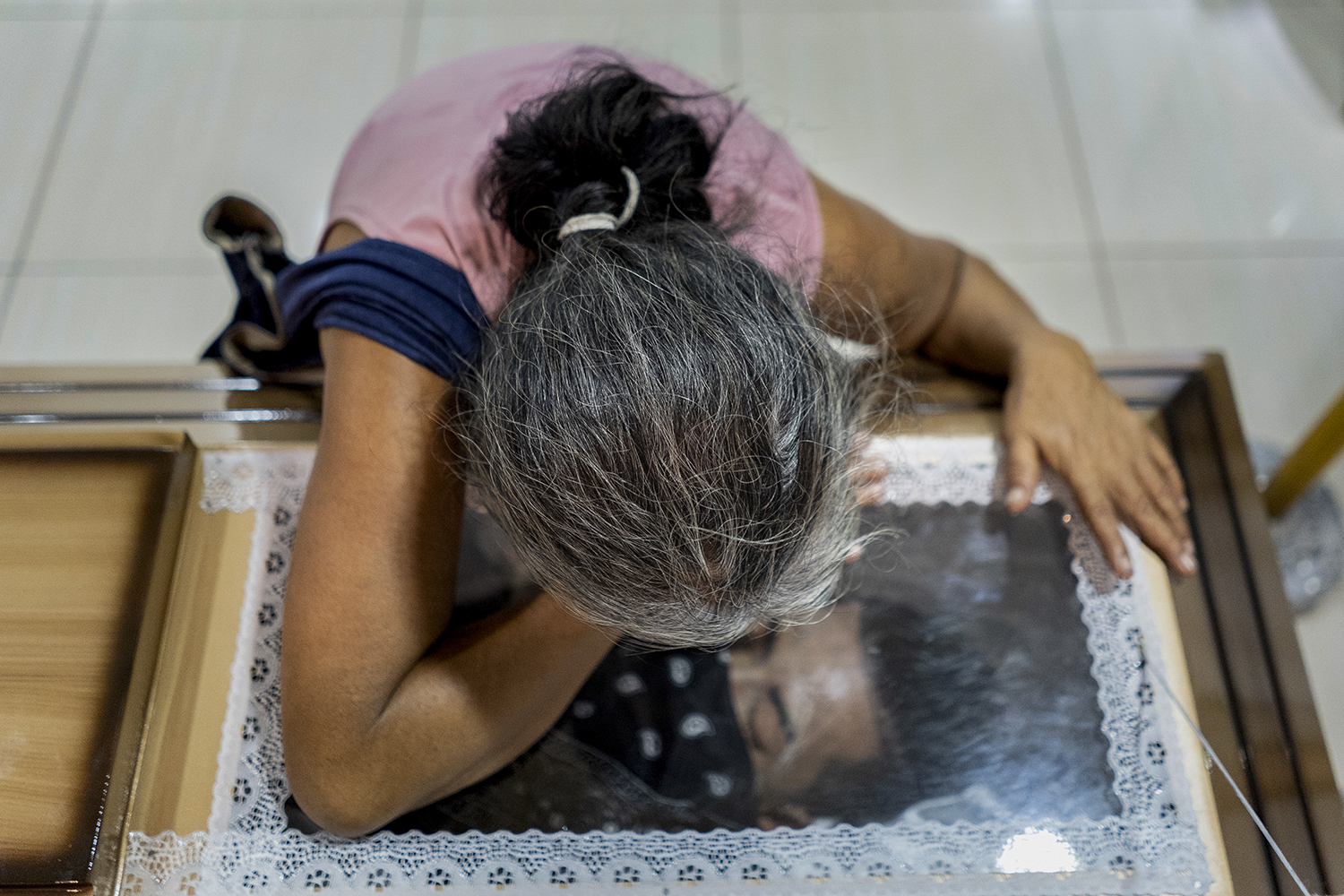 Gloria, whose last name has been omitted to protect her identity, mourns her 25-year-old son, Stanley, at his wake in San Martín, San Salvador, on Nov. 7, 2018. Stanley's face is covered by a bandana after he was strangled by members of La 18 for not fulfilling the missions the gang asked of him, his mother said. He is also survived by his wife and 6-year-old son.
