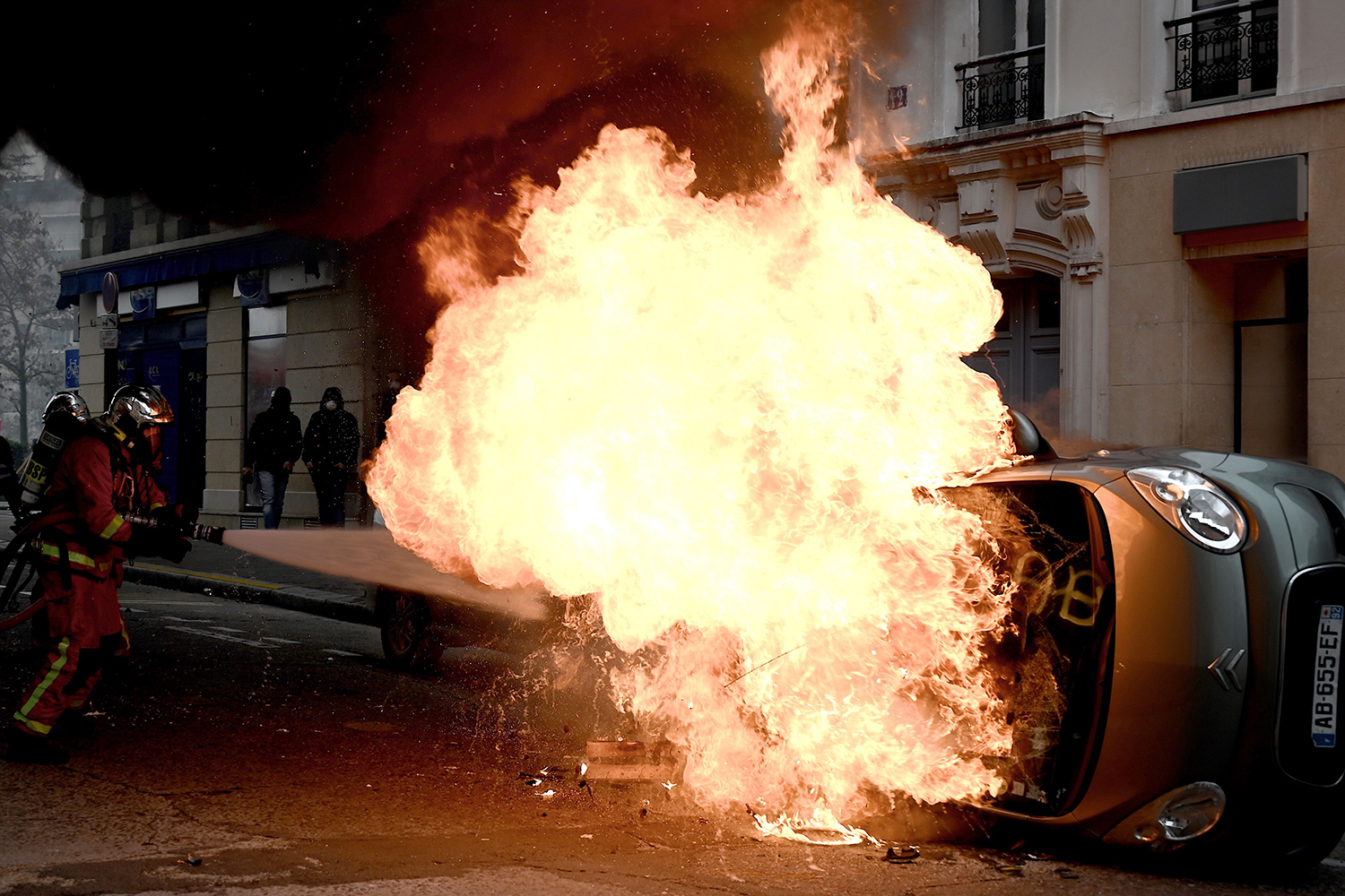 A firefighter tries to extinguish a burning car on place d'Italie in Paris on the sidelines of a demonstration of the yellow vests marking the first anniversary of the movement on Nov. 16. PHILIPPE LOPEZ/AFP via Getty Images