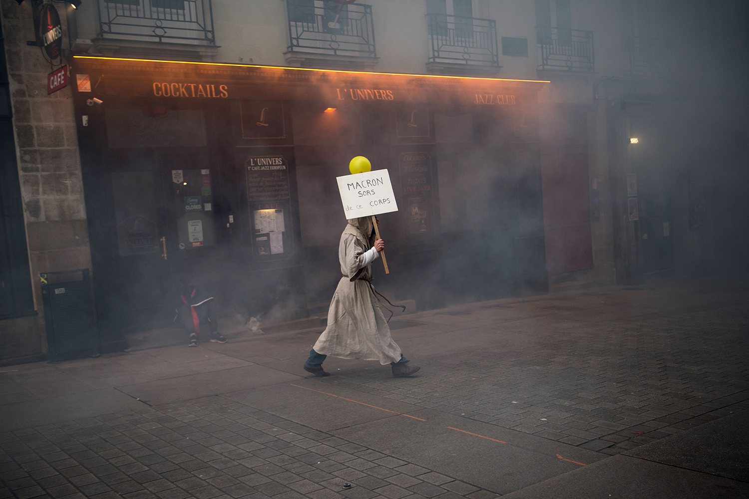 """A man wearing a monk suit holds a placard reading """"Macron get out this body """" during a yellow vest demonstration in Nantes, western France, on Nov. 16. LOIC VENANCE/AFP via Getty Images"""
