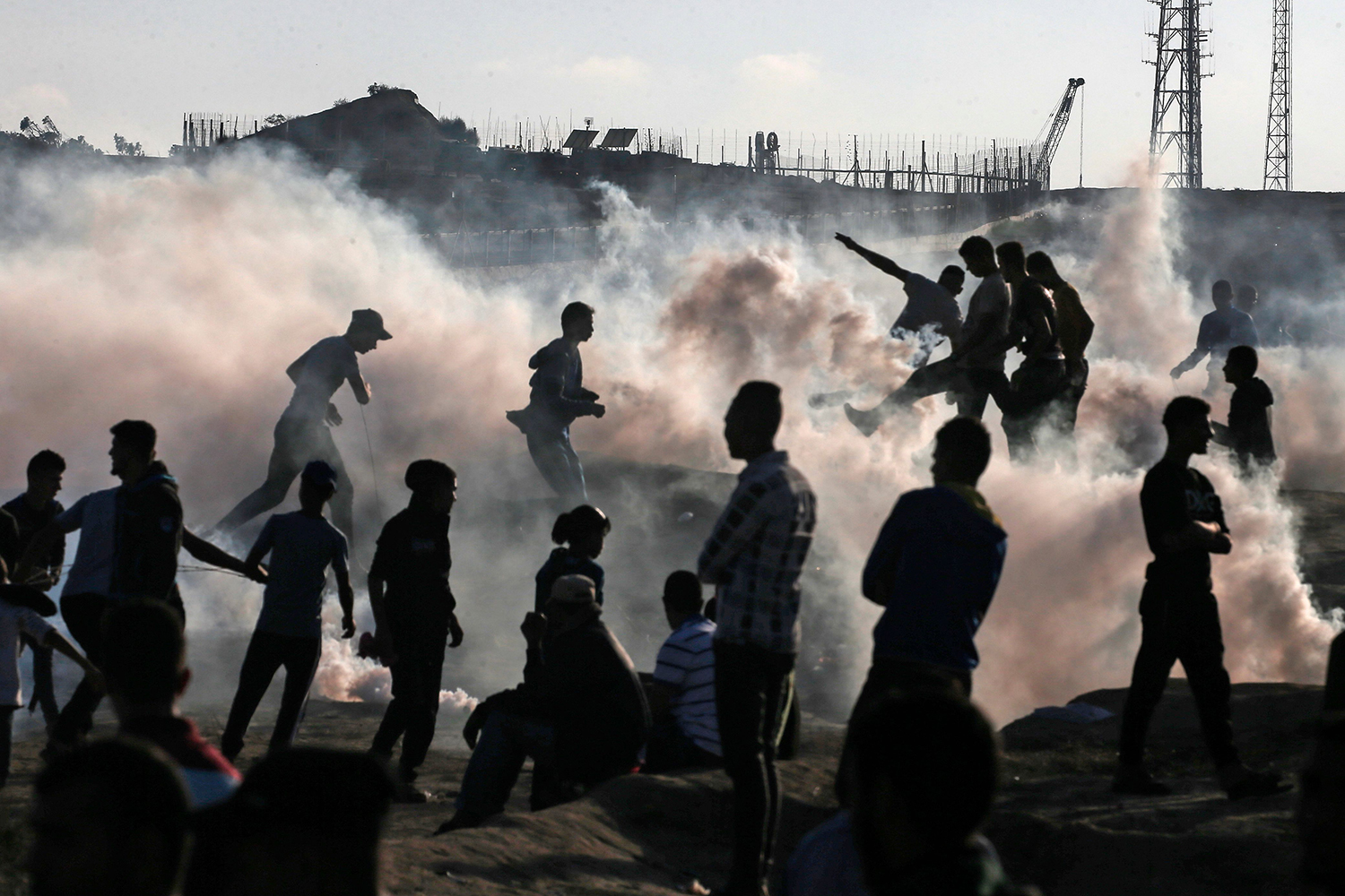 Palestinian protesters stand amid tear gas canisters fired by Israeli forces during a demonstration along the border with Israel east of Bureij in the central Gaza Strip on Nov. 1. MAHMUD HAMS/AFP via Getty Images