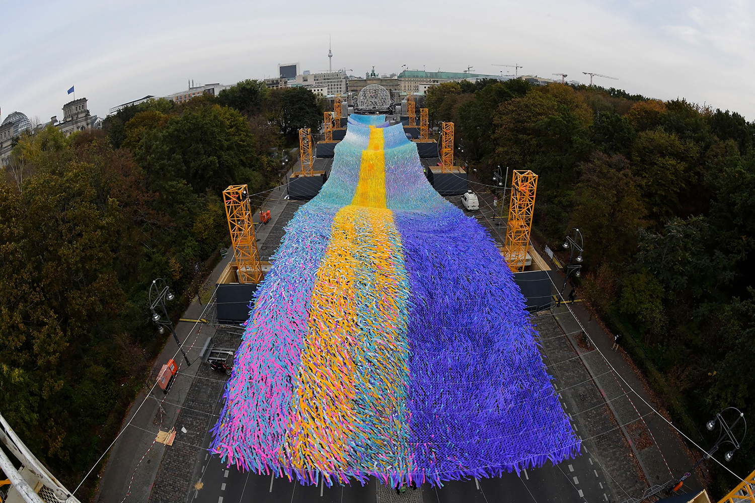 The installation Visions in Motion by artist Patrick Shearn is seen during a test run between the Brandenburg Gate and the Victory Column in Berlin on Nov. 1 ahead of the 30th anniversary of the fall of the Berlin Wall. TOBIAS SCHWARZ/AFP via Getty Images