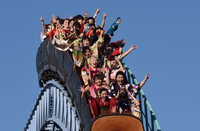Japanese women dressed in kimonos take a ride on a roller coaster