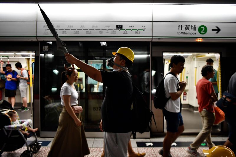 A protester holds up an umbrella at Prince Edward MTR station as he and other protesters take a vote on which location to proceed to next in Hong Kong on Aug. 10.