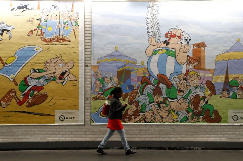 A woman walks next to posters commemorating the 60th anniversary of France's famous comic characters Asterix and Obelix in Paris on Oct. 9.