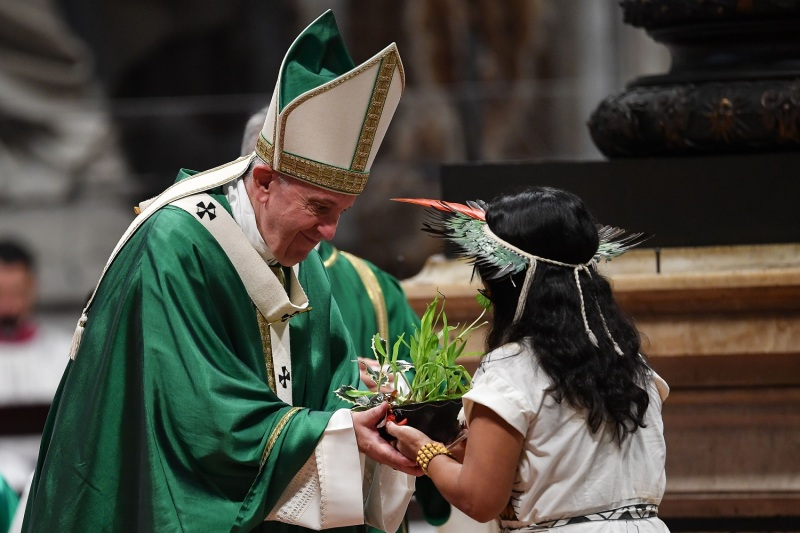 Pope Francis receives a plant offered by an indigenous woman from the Amazon as he celebrates the closing mass of the Synod on the Amazon on October 27, 2019 at Saint Peter's Basilica in the Vatican.