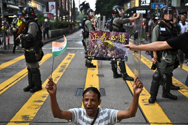 A man waves an Indian flag near Chungking Mansions, a popular haunt among minority South Asians and Africans in Hong Kong, as police keep watch at a crosswalk during a pro-democracy rally in Tsim Sha Tsui district on Oct. 27.