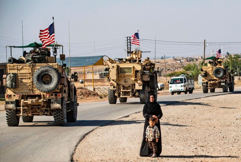 A convoy of U.S. armored vehicles patrols the northeastern Syrian town of Qahtaniyah