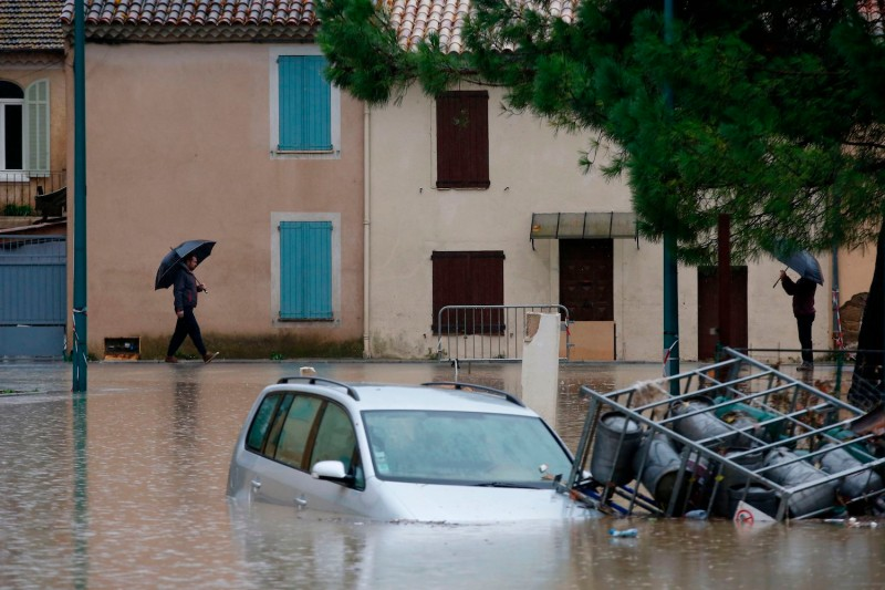 A man walks with an umbrella as a car sits underwater in a flooded area following heavy rains in Le Muy in southeastern France on Nov. 24.