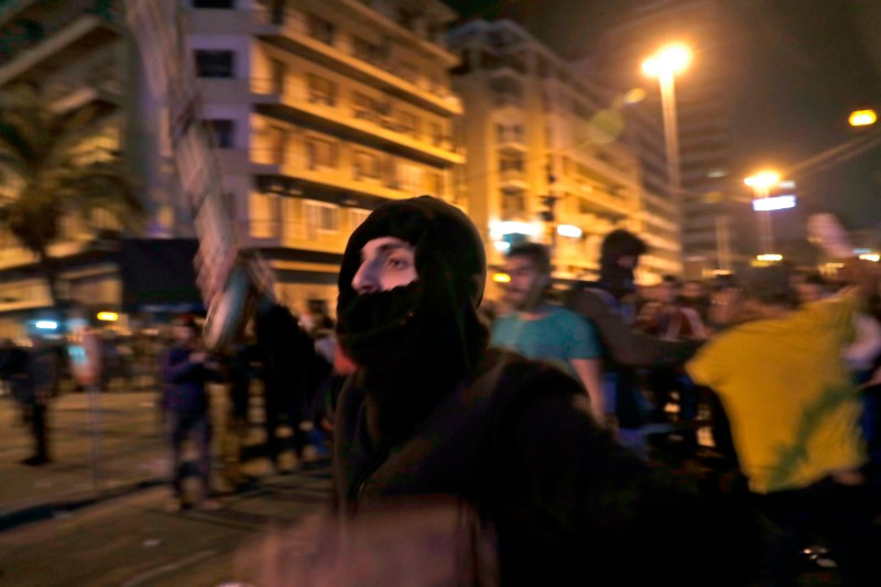 A Lebanese anti-government demonstrator waves a stick while confronting supporters of the Shiite groups Hezbollah and Amal in Beirut on Nov. 25.