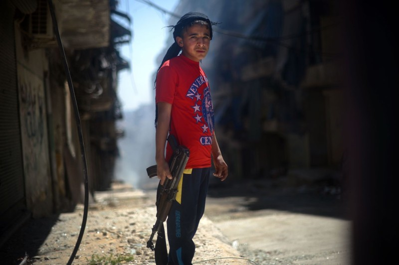 A Syrian boy holds an AK-47 assault rifle