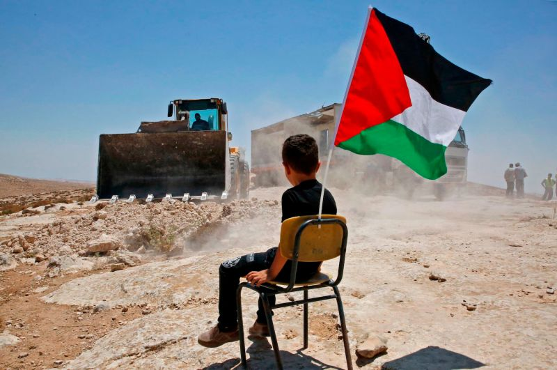 A Palestinian boy sits on a chair as Israeli authorities demolish and relocate a school site
