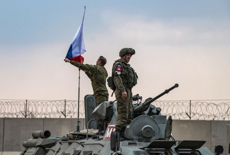 Russian troops raise a national flag on top of their armored personnel vehicle while on patrol with Turkish forces in Syria's northeastern Hasakah province on Nov. 1.