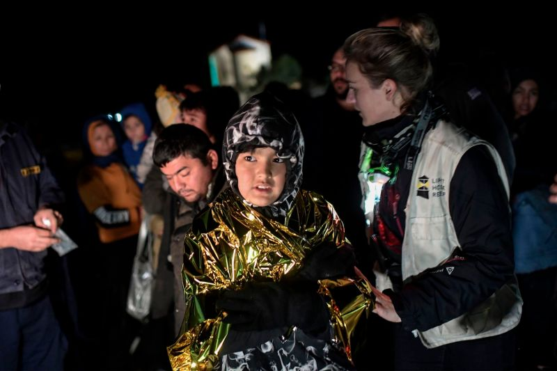 A volunteer helps a young boy following a sea rescue operation near the Greek island of Lesbos on Nov. 27.
