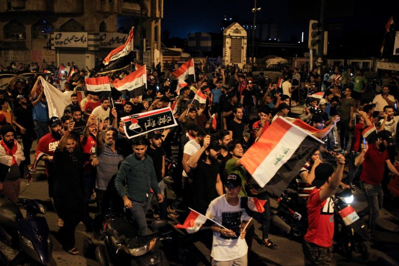 People wave Iraqi national flags as they take part in an anti-government demonstration at Tahrir Square in Baghdad on Oct. 24.