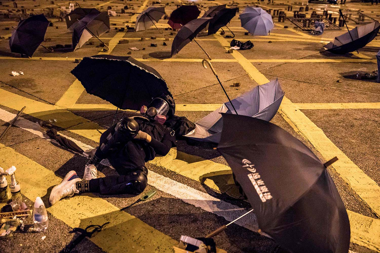 A protester rests on the ground on a blocked road at the Hong Kong Polytechnic University on Nov. 14. DALE DE LA REY/AFP via Getty Images