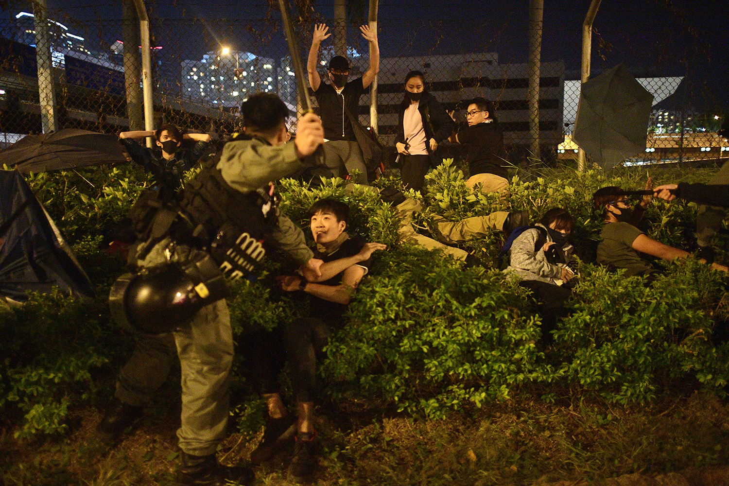 Police detain protesters and students after they tried to flee outside the Hong Kong Polytechnic University campus on Nov. 19. NICOLAS ASFOURI/AFP via Getty Images