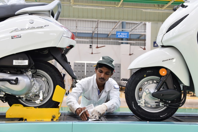 An employee takes notes as he inspects fully assembled Honda Activa scooters at a factory on the outskirts of Bangalore on Aug. 2, 2017.