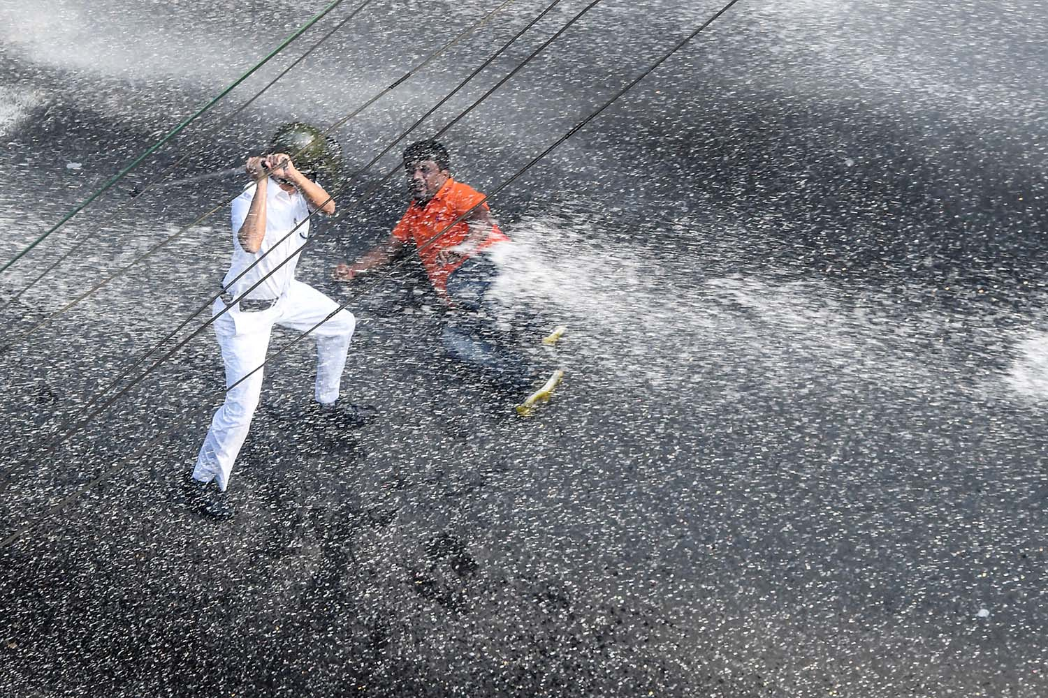 A police officer charges a Bharatiya Janata Part protester with a baton as police fire a water cannon during a protest against the Trinamool Congress-led state government in Kolkata, India, on Nov. 13.  DIBYANGSHU SARKAR/AFP via Getty Images