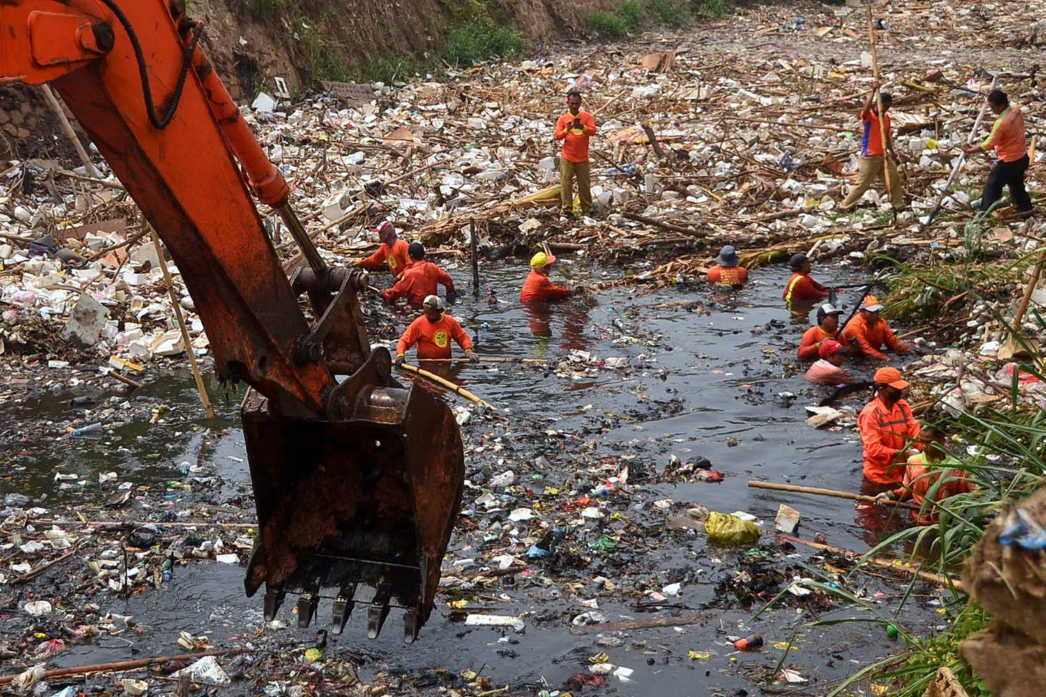 Workers clean up tons of waste from Pete river in Bekasi, West Java, on Nov. 12. REZAS/AFP via Getty Images