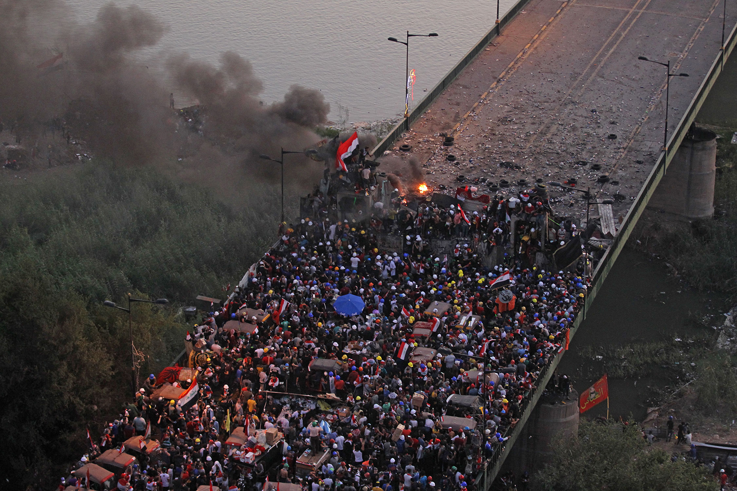 Iraqi protesters gather on al-Jumhuriya bridge which leads to the high-security Green Zone, during ongoing anti-government demonstrations in Baghdad on Oct. 31. AHMAD AL-RUBAYE/AFP via Getty Images