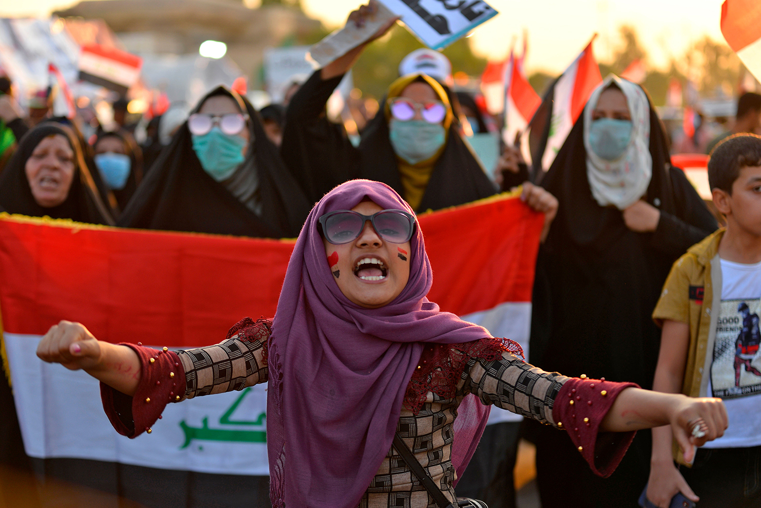 Iraqi women chant slogans and wave the national flag during protests in Najaf on Oct. 30. -/AFP via Getty Images