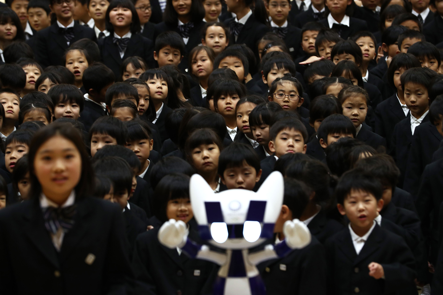 Schoolchildren pose for a picture with Miraitowa, the robot-like mascot for the Tokyo 2020 Olympic Games, during a ceremony at Hoyonomori elementary school in Tokyo on Nov. 18. BEHROUZ MEHRI/AFP via Getty Images