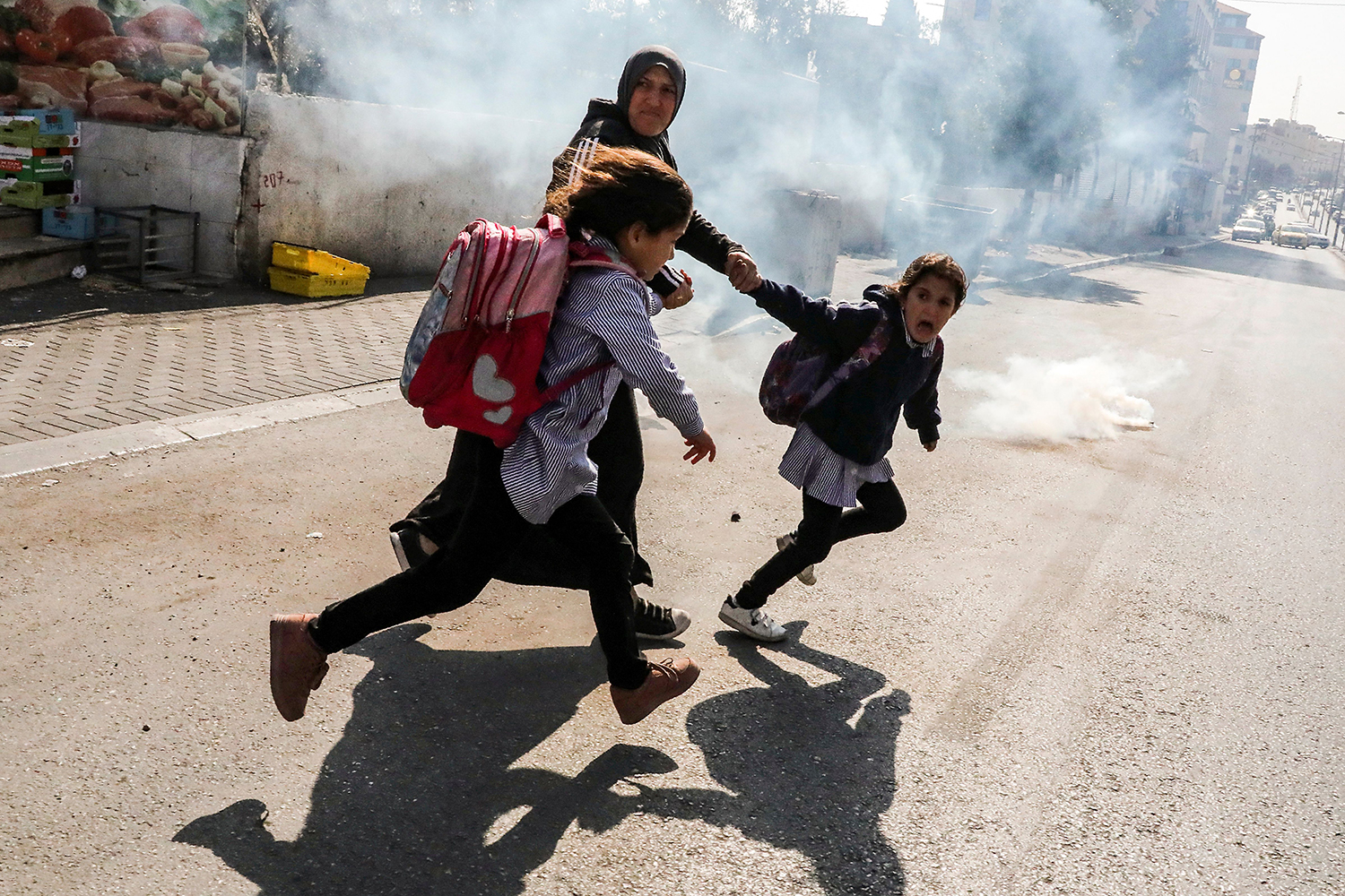 A woman and two school girls attempt to flee from tear gas fired at Palestinian journalists gathering for a demonstration near Israel's separation barrier in Bethlehem in the occupied West Bank on Nov. 17. HAZEM BADER/AFP via Getty Images