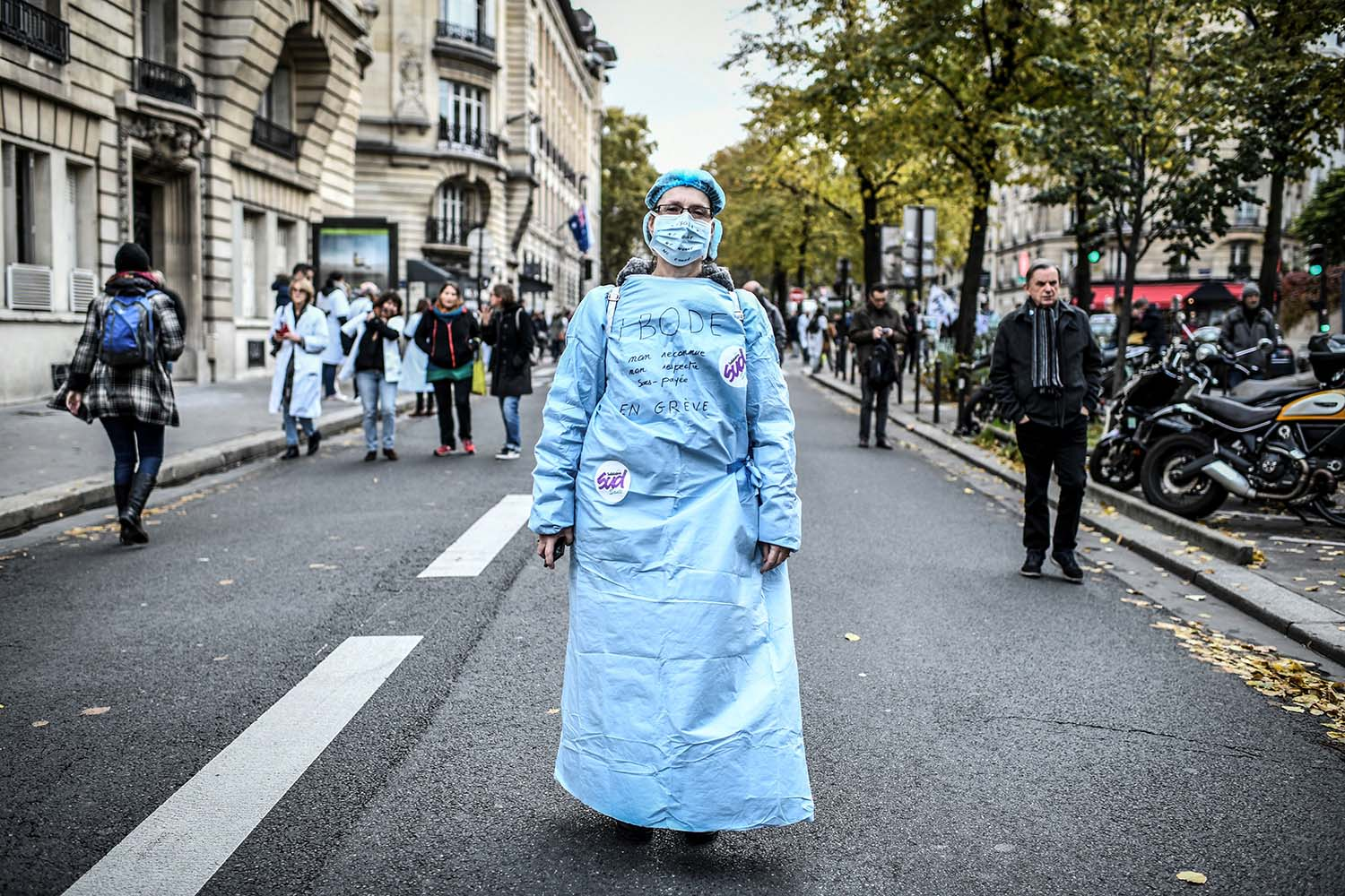 "An operating room nurse wearing a surgical mask and gown with the lettering reading ""IBODE (Infirmier de bloc operatoire),"" which translates as ""unrecognized, not respected, underpaid"" takes part in a nationwide day of protest in Paris on Nov. 14, calling for an emergency plan for public hospitals. STEPHANE DE SAKUTIN/AFP via Getty Images"