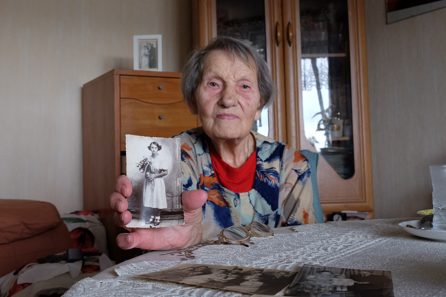 Irena Paduch holds up an old photo of herself at her apartment in Lodz in September.